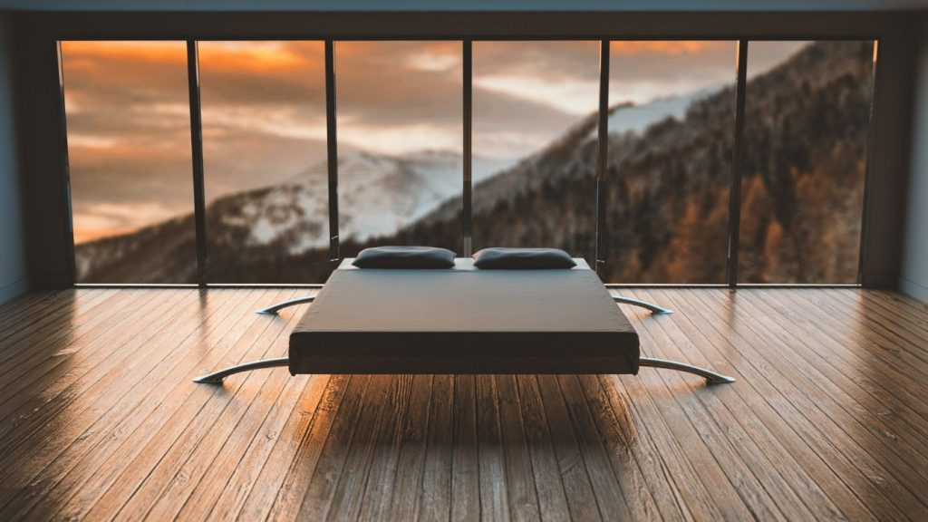 unique mattress foundation in middle of the room with sunset behind