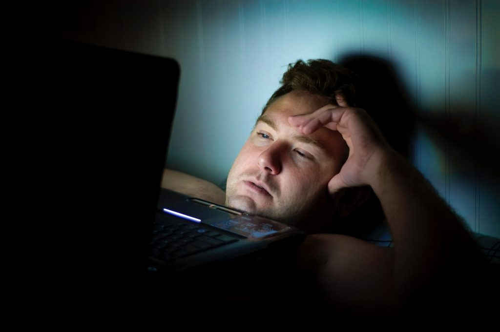 Man lay in bed with laptop