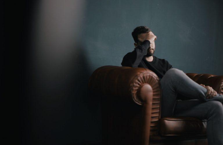 stress, headaches man sitting in sofa